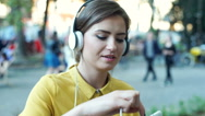 Happy woman wearing headphones and watching something on tablet Stock Footage