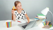 Schoolgirl holds her lollipop and typing something in her laptop Stock Footage
