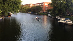 Athletes on a crew boat row down a canal in Amsterdam in the Netherlands.  Stock Footage