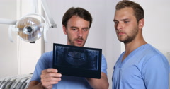Stomatologist Men Collaboration Examine Holding Radiography Stomatology Cabinet Stock Footage