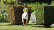 Focus pull from young woman walking to water fountain Stock Footage