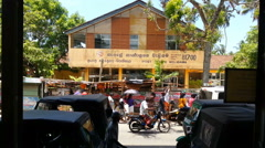 Busy street with cars, tuk tuks, pedestrians passing by post office and market Stock Footage