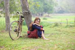 Young asian women inattentive sitting next to tree with bike in rice field Stock Photos