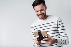 Joyful bearded man smiling and using portable gamepad Stock Photos