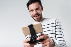 Energized bearded man using portable gamepad Stock Photos
