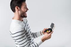 Emotional bearded man using portable gamepad Stock Photos