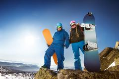 Snowboarders posing on blue sky backdrop in mountains Stock Photos