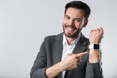 Smiling bearded man demonstration his smartwatch Stock Photos