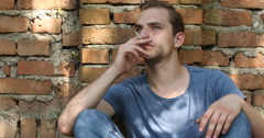 Young Hipster Man Smoking a Cigarette Back on Red Brick Wall Building House Day Stock Footage