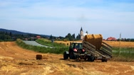 Farmers harvest grain from the field (farmer loads haystacks on the tractor)  Stock Footage
