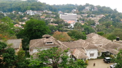 Green tropical city from above, buildings hidden among trees, peaceful cityscape Stock Footage