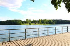 Side view on lake (recreational dam, water area) from wooden pier with fence Stock Photos
