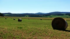 Field in countryside with haystack - forests in background - sunny day Stock Footage