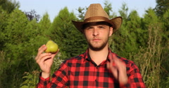 Serious Young Farmer Man Holding Pear and Showing OK Sign in Countryland Orchard Stock Footage