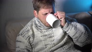 Sick man blowing his nose in the tissue, snotty drinking warm healing tea Stock Footage
