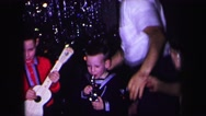 1974: little kids at christmas party play instruments while adults dance around Stock Footage