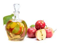 Apple cider vinegar in a glass vessel and red apples Stock Photos