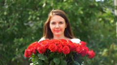 Footage woman holding a bouquet of roses outdoors. 4k Stock Footage