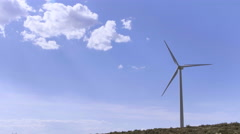Modern Wind Turbine Generating Sustainable Energy with Blue Sky Background Stock Footage