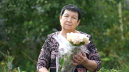Footage elderly woman holding a bouquet of roses outdoors. 4K Stock Footage