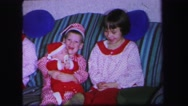 1974: brothers and sisters holding baby on the couch at christmas time LYNBROOK Stock Footage