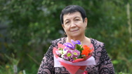 Footage elderly woman holding a bouquet of flowers outdoors. 4K Stock Footage