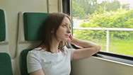 Young woman looking out the window of a train Stock Footage