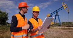 Engineer Men Discuss Petroleum Installations Hold Clipboard Show Plans Teamwork Stock Footage