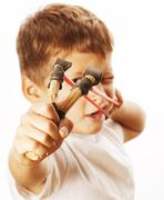 Little cute angry real boy with slingshot isolated Stock Photos