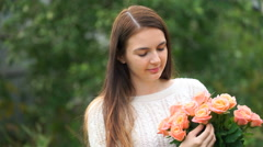 Footage woman holding a bouquet of flowers outdoors. 4k Stock Footage