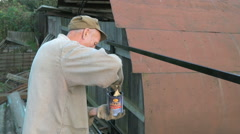Adult man paints the iron fence using black paint Stock Footage