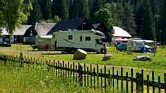 Campsite in nature next to the forest - camp vans with people  Stock Footage