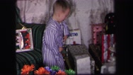 1974: a little boy in purple striped pajamas retrieving a gift and opening it up Stock Footage