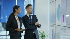 4KBusinessman & woman in discussion looking at video screen with charts & graphs Stock Footage