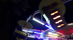 Amusement park spinning wheel ride fast rotate at night Stock Footage