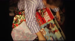 1974: kids unpacking presents before mother in the room with decorated tree Stock Footage