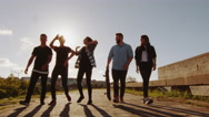 Group of Happy Teenagers Laughing, Raising Hands, Jumping While Moving Forward Stock Footage
