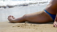 Woman lying on the sand, the sea waves splashing in her body, slow motion Stock Footage