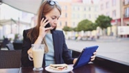 Businesswoman talking on a Phone using Tablet in outdoor Cafe. SLOW MOTION. Stock Footage