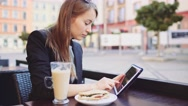 Businesswoman uses Tablet in street Cafe, drinks Coffee, has lunch. SLOW MOTION Stock Footage