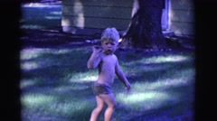 1961: a shirtless young boy in shorts looks confused as he walks in his yard Stock Footage