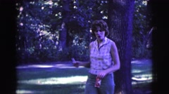 1961: woman walks through wooded area carrying cigarette to give to man. Stock Footage