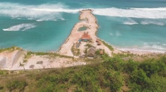 Aerial view of artificial mound in ocean behind a cliff Stock Footage