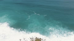 Aerial view of artificial mound in ocean and cliff behind it Stock Footage