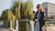 Young Businesswoman Using SmartPhone in the Sunny City. SLOW MOTION STEADICAM Stock Footage