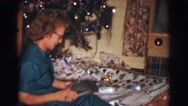 1961: woman opening a gift under the christmas tree. CLARKSDALE, ARIZONA Stock Footage