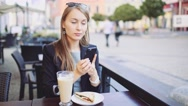 Businesswoman uses Smartphone in street Cafe, drinks Coffee. SLOW MOTION Stock Footage