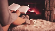 Woman Reading a Book by the Cozy Fireplace. 4K Stabilized shot. Stock Footage