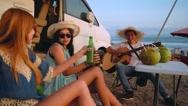Three friends on beach picnic near camper van Stock Footage