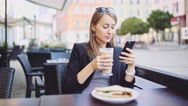 Young Businesswoman uses Smartphone in street Cafe, drinks Coffee. SLOW MOTION Stock Footage